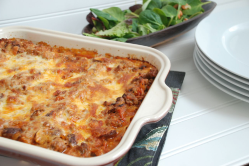 Irish lasagna in a baking dish with a green side salad