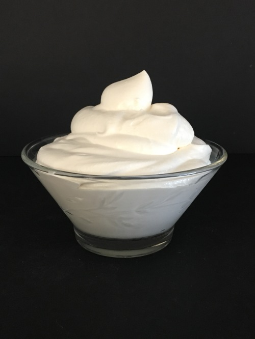 A glass bowl filled with maple vanilla whipped cream