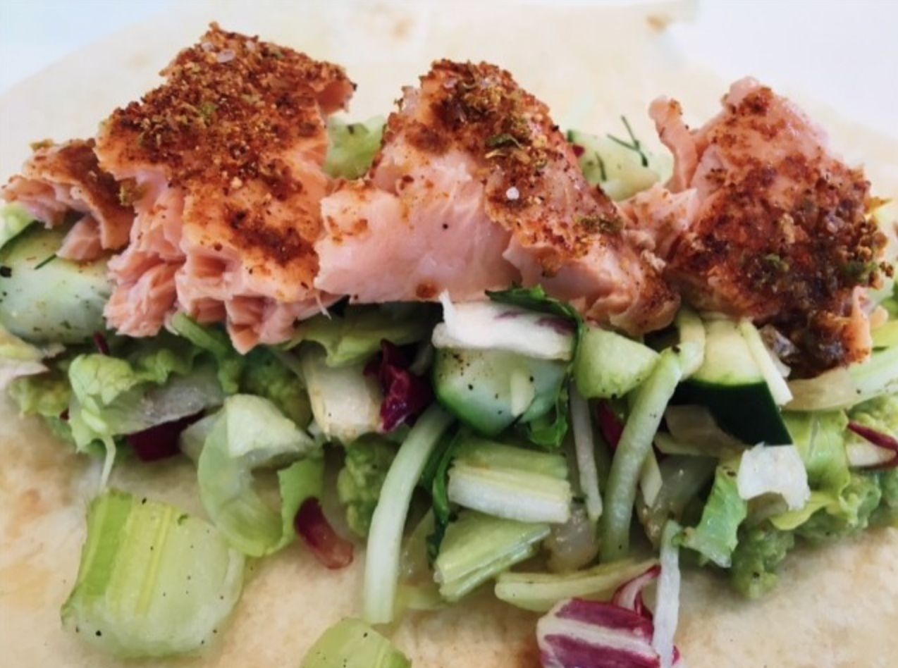 One salmon taco on a bed of lettuce and cucumber