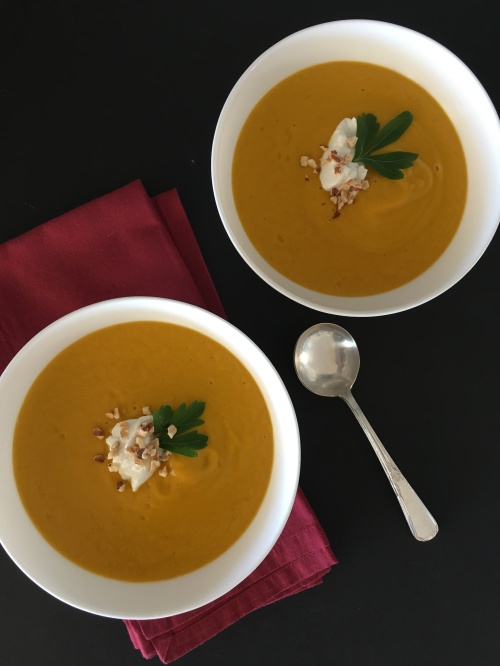 Two white bowls filled with roast carrot and cumin soup