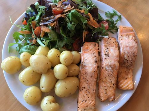 Oven roasted salmon, boiled potatoes, and a green salad on a white plate.