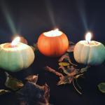 Three candles in pumpkins with autumnal leaves