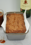Fresh Apple Cake in a loaf pan with a pot of Irish Whiskey Caramel Sauce