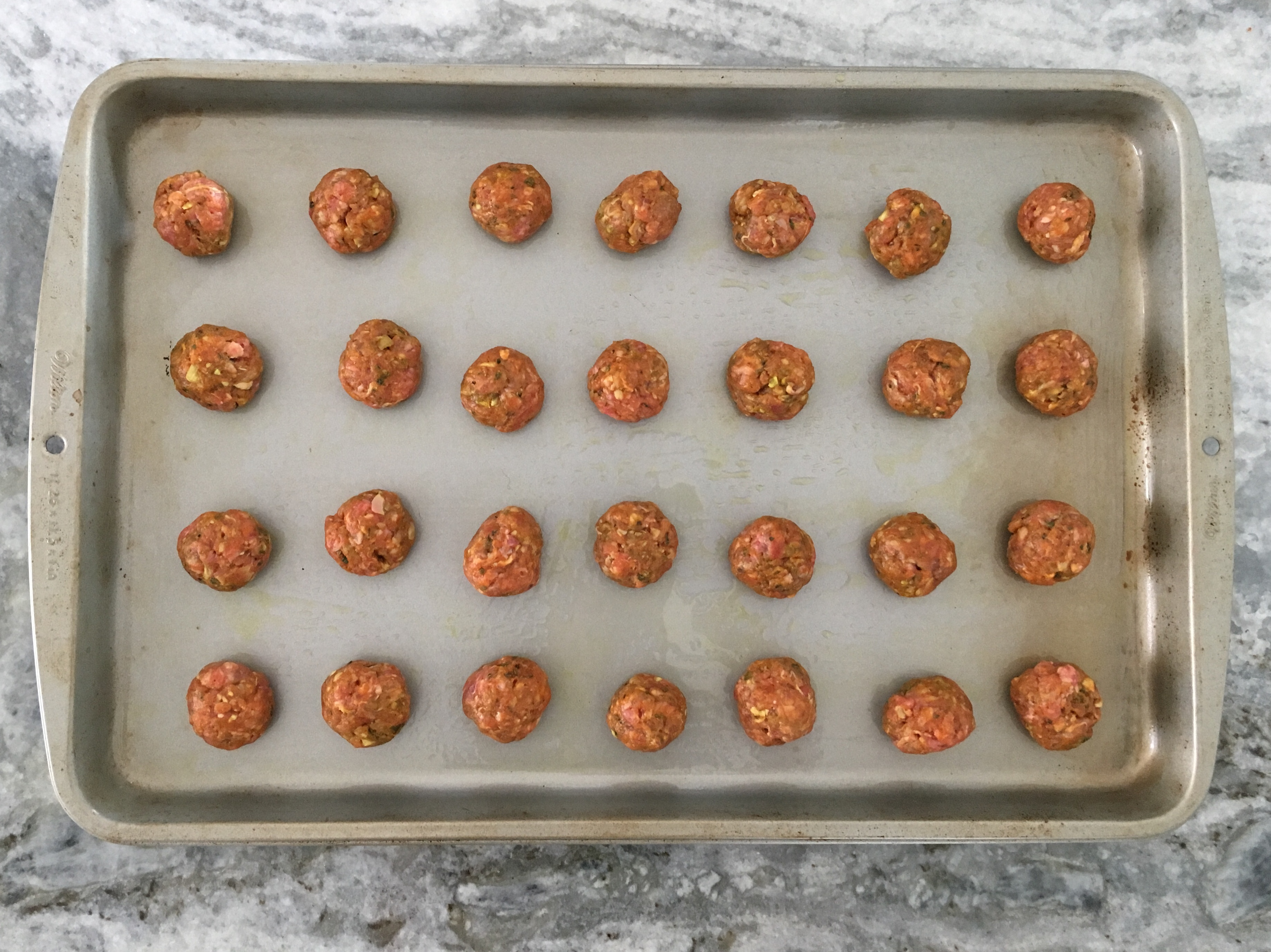 Ready for the oven: raw sheet pan meatballs
